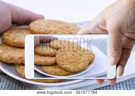 Woman Hand Holding Smart Phone Take Photo Of Homemade Shortbread Cookies Made Of Oatmeal Stacked In
