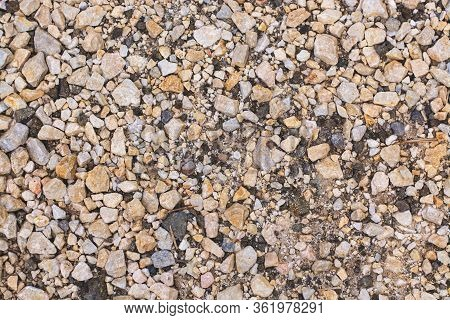 Closeup Of Yellow And Black Rocky Gravel Ground Background