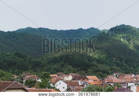 Red Roofs Of Small Town Homes Against Green Lush Mountain Hills, Cloudy Sky With Towers And Cables O