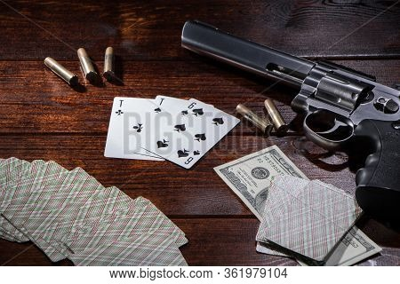 Gambling In Poker Or Blackjack For Money. On A Wooden Table Are A Pistol With Cartridges, Cash Dolla