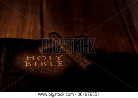Crucifix And Holy Bible On Wooden Table.