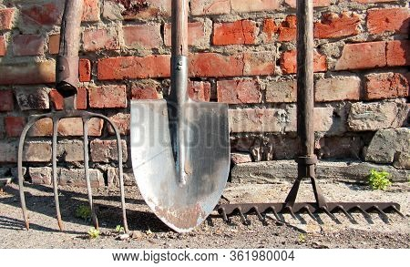 Garden Tool Set. Old Rusty Rake, Shovel, Pitchfork On Brick Wall Background