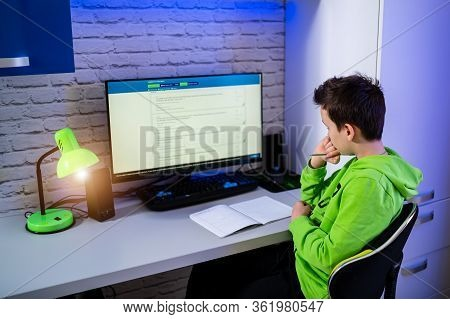 Teenage Boy Studing At Home. Young Boy At Computer Doing Tests.study In Quarantine. Schoolboy During