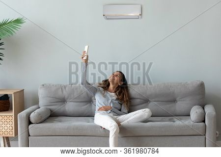 Smiling Woman Relaxing On Couch, Using Air Conditioner Remote Controller