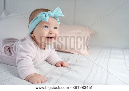 Newborn Baby Lies On Its Stomach And Smiles. A Child With Blue Eyes And A Blue Headband. Cute Baby W