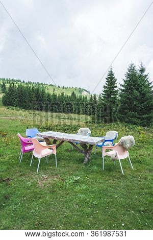Group Of Colorful Plastic Chairs Around Wooden Table On Hillside Slope Covered With Grass And Pine T