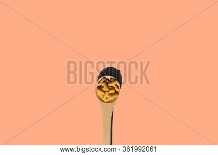 Super Food Concept Wooden Spoon With Turmeric Curcumin Capsules On Beige Background