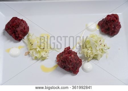 Beef Tar-tar. Meat Tar Tar On A White Plate, On A White Background. A Dish From A Restaurant