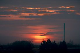 Beautiful Sunset Over An Industrial Facility At Dawn With Trees In Front And A Large Chimney