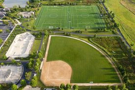 Aerial view of a multi-use playfield with baseball/softball diamonds, a soccer/lacrosse field and a skate park.