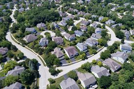 Aerial view of a tree-lined, suburban neighborhood with cul-de-sac in summer.