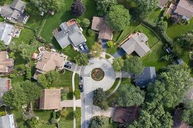 Aerial view of a tree-lined neighborhood in a cul-de-sac in a Chicago suburb in summer.