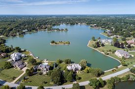 Aerial view of a tree-lined, upscale suburban neighborhood with a large lake in summer.