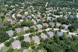 Aerial view of a tree-lined, upscale suburban neighborhood with winding streets in summer.
