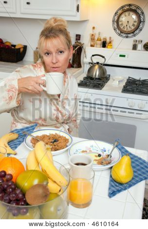 Woman Sipping Coffee In Kitchen