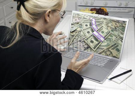 excited Frau in Küche mit dem Laptop Geld