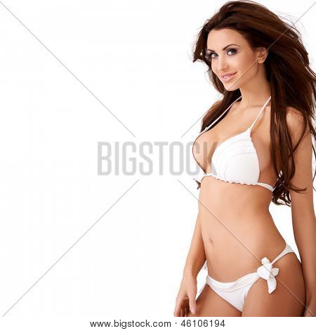 Smiling sexy young brunette woman with a lovely figure posing in a white bikini  three quarter isolated studio portrait