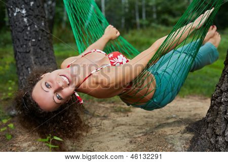 Young smiling barefooted woman swing in hammock, head thrown back
