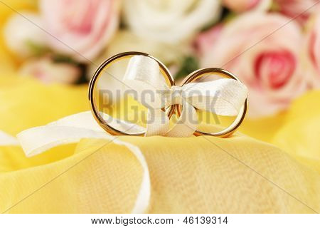 Wedding rings tied with ribbon on bright background