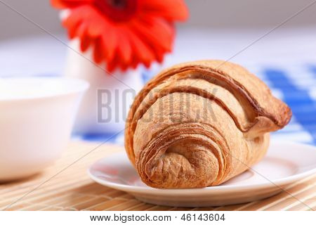 Continental breakfast with croisant on white plate