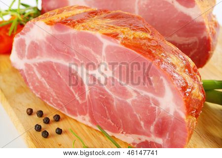 macro detail of smoked pork neck on a wooden cutting board