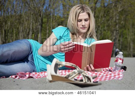 Attractive blonde woman reading a book on a sandy beach on a beautiful, sunny, spring day.