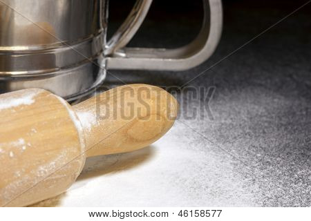 Rolling pin and sifter, over floury stone bench.