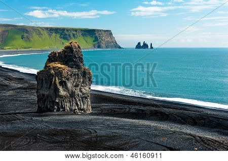 Beautiful rock formation on a black volcanic beach at Cape Dyrholaey, the most southern point of Iceland. poster