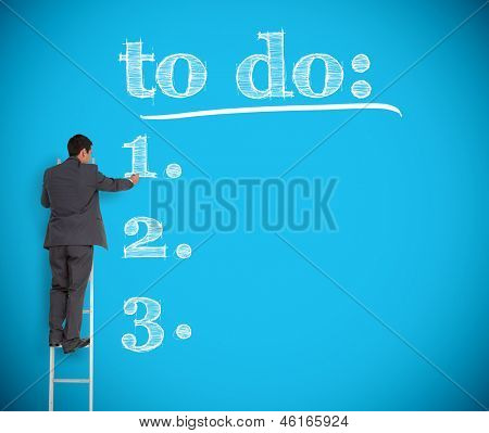 Businessman writing a to do list on a giant blue wall helped by a ladder
