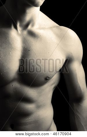 Man with naked muscled torso against black background