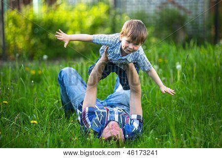 Vader en zoon spelen liggen op het gras in het park