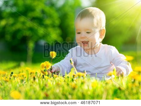 Baby Girl On A Green Meadow With Yellow Flowers Dandelions On The Nature
