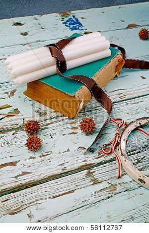 Candles tied with ribbon on antique book placed on the old grunge table background
