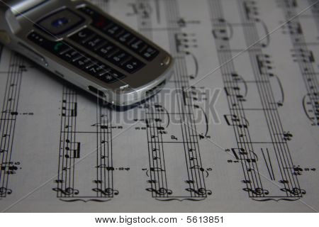 Gray cell phone on sheet music. No visible logos. poster