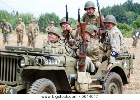 World War II re-actors riding in a period jeep