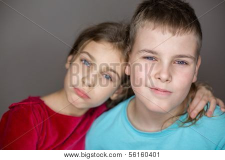 Portrait of sister and brother hugging in the studio, focus on a boy.