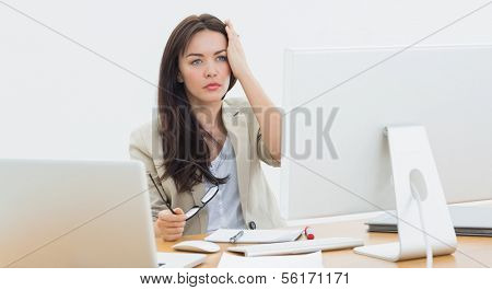 Serious young casual business woman in front of computer at a office