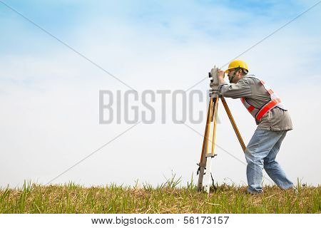 professional Surveyor engineer making measure on the field poster