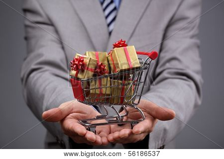 Businessman with shopping cart full of gift boxes concept for gift shopping, business gift, christmas or valentine's day gift