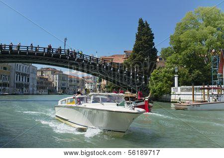 Venice, Veneto, Italy - May 24: Taxi boat driving under Ponte dell'Accademia bridge on Grand Canal. circa May 24, 2011 in Venice, Veneto, Italy