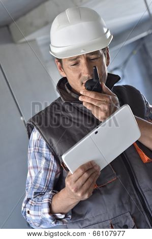Entrepreneur on building site using walkie talkie poster