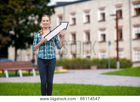happiness, direction and people concept - smiling young woman arrow poiting up