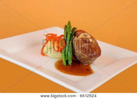 A plate with lamb asparagus mashed potatoes and sauce poster