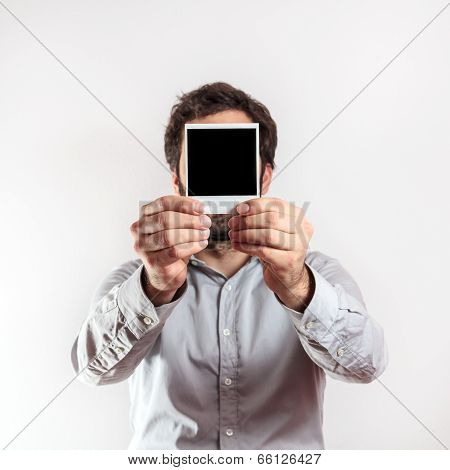 young man with empty photo frame i over the face