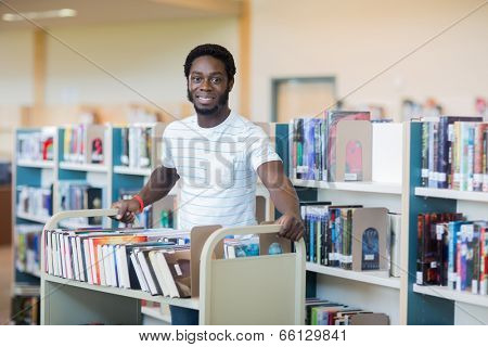 Portrait of young male librarian with trolley of books in library