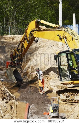 site worker and driver with large bulldozer, digger in action, road-works and construction industry, close-ups view.