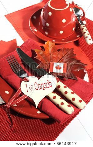 Happy Canada Day dinner party table setting in red and white polka dot china and cutlery on Canadian Maple Leaf flag with heart gift tag and sample text or copy space. poster