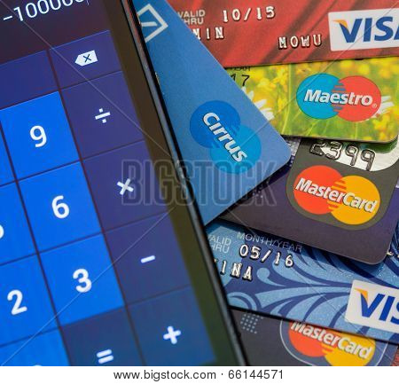TOMSK, RUSSIA - JUNE 03, 2014: Calculator lying on table over pile of different credit cards: Visa, MasterCard, Cirrus, Maestro.