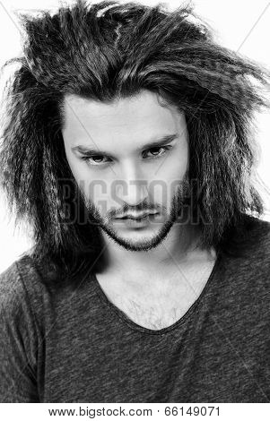 Portrait of a modern young man in casual clothes looking unwelcoming from under his brows. Hairstyle. Isolated over white.
