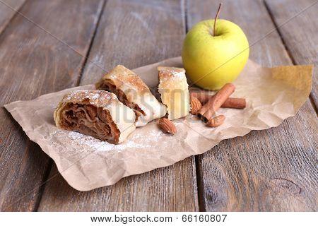 Tasty homemade apple strudel  on paper napkin, on wooden background